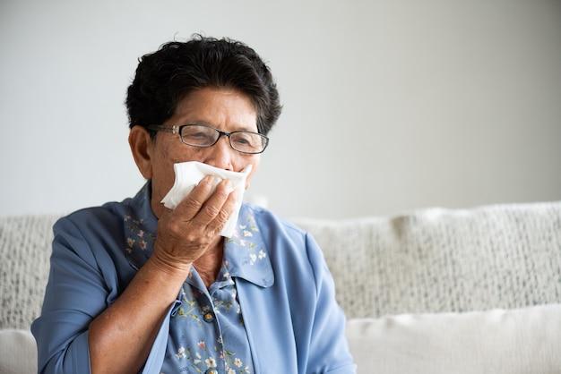 Zieke aziatische oude vrouw die papieren zakdoekje dichte mond gebruiken terwijl hoest