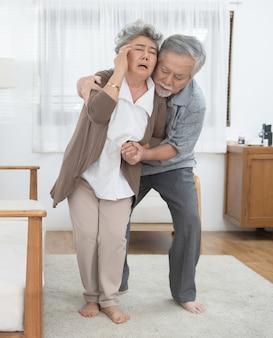 Zieke aziatische senior vrouw is flauwgevallen en gevallen op de vloer, grootvader helpen bejaarden bewusteloos op de grond liggen.