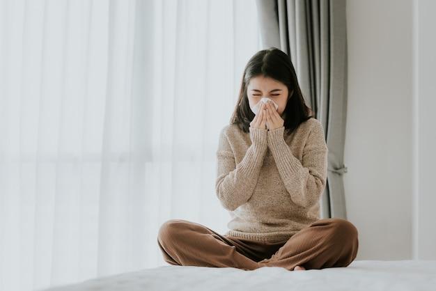 Zieke aziatische vrouw die een weefsel gebruikt om thuis te niezen