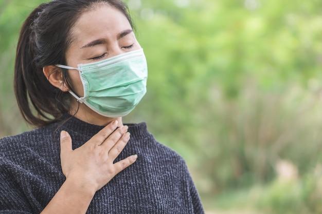 Zieke aziatische vrouw draagt masker met verkoudheid en griep