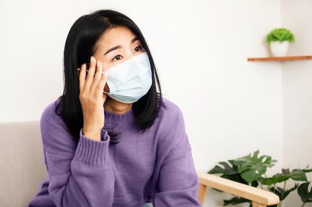 Zieke aziatische vrouw met gezichtsmasker met hoofdpijn