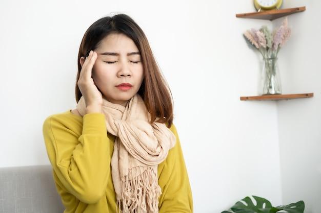 Zieke aziatische vrouw met hoofdpijn, migraine zittend op de bank