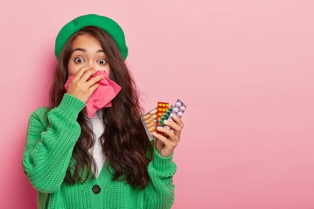 Zieke aziatische vrouw verkouden tijdens natte herfstdag, heeft lopende neus, houdt verschillende pillen voor het genezen van ziekte, draagt groene baret en trui