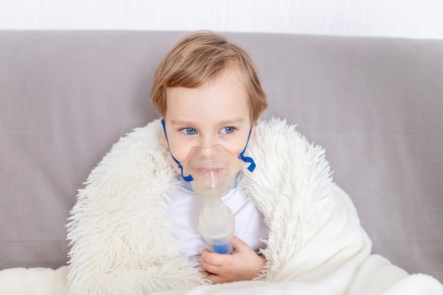 Zieke babyjongen met inhalator behandelt keel thuis, het concept van gezondheid en inhalatiebehandeling