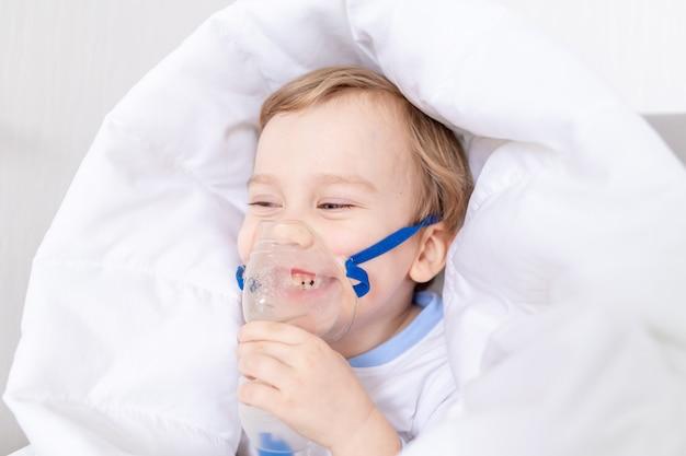 Zieke babyjongen met inhalator behandelt thuis keel, het concept van gezondheid en inhalatiebehandeling