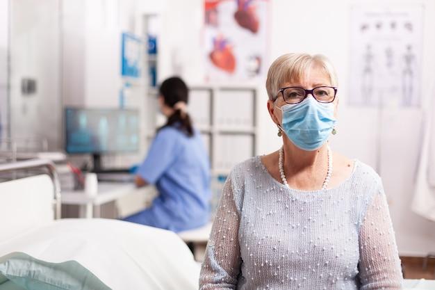 Zieke bejaarde geduldige vrouw die op diagnose van arts wacht tijdens behandeling die gezichtsmasker draagt