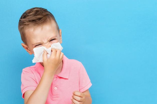 Zieke blanke jongen blaast neus in weefsel