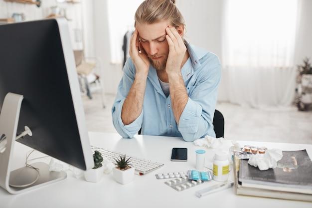 Zieke blanke man zit op kantoor, knijpt in tempels vanwege hoofdpijn, werkt aan computer, kijkt naar het scherm met pijnlijke uitdrukking op gezicht, probeert zich te concentreren, omringd door medicijnen
