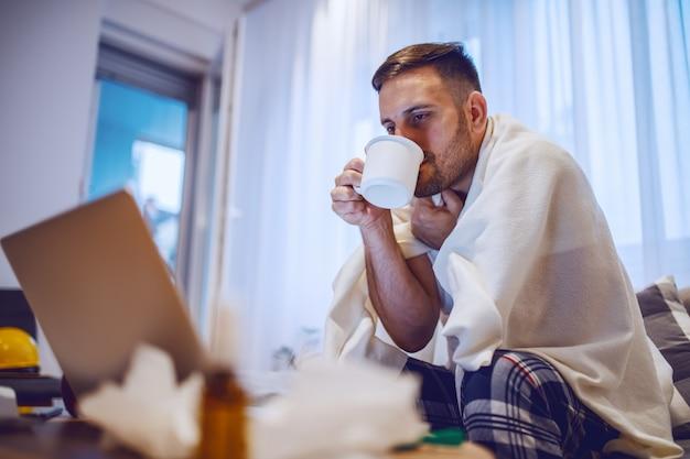 Zieke blanke ongeschoren man in pyjama bedekt met deken zittend op de bank in de woonkamer, het drinken van thee en kijken naar laptop.