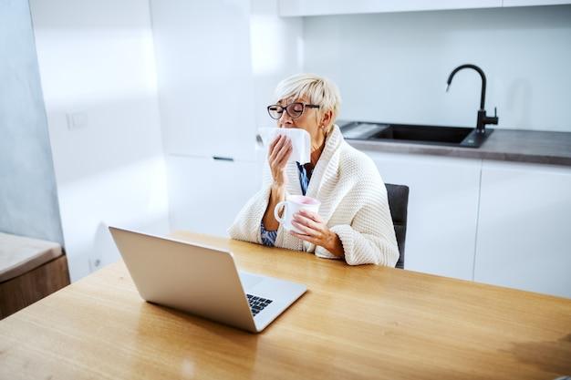 Zieke blonde senior vrouw bedekt met een deken aan eettafel zitten en niezen