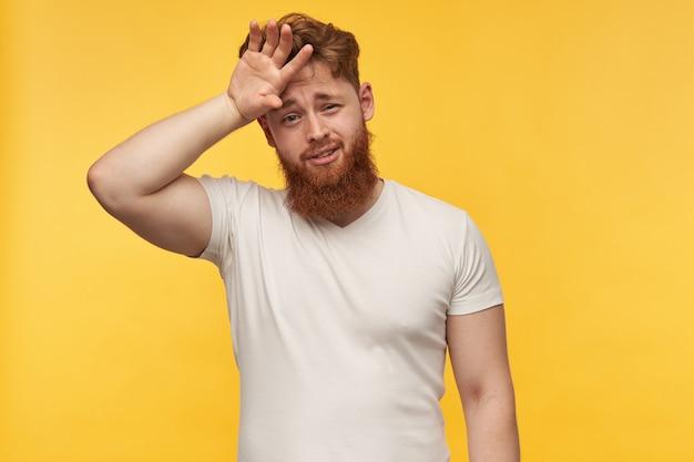 Zieke en moe uitziende man met een grote baard en rood haar, draagt een blanco t-shirt en raakt zijn voorhoofd met de hand aan.