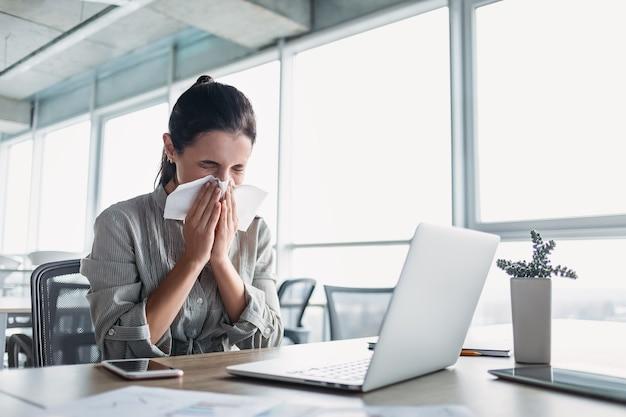 Zieke en overwerkte zakenvrouw die aan het bureau op kantoor zit en haar neus snuit
