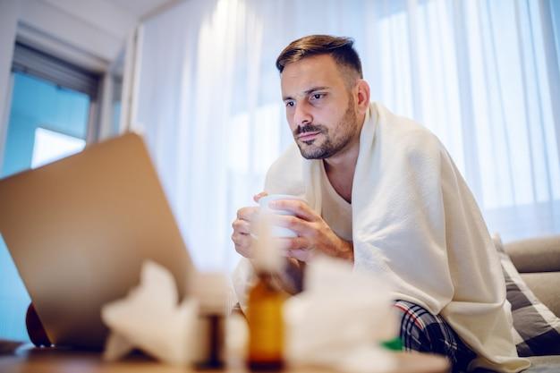 Zieke ernstige werknemer in pyjama bedekt met deken het drinken van thee en kijken naar laptop zittend op de bank in de woonkamer.