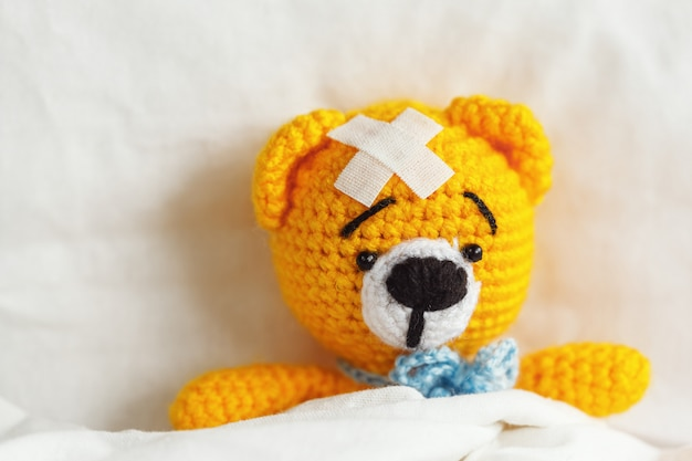 Zieke gele teddybeer met pleister op hoofd in witte slaapkamer.