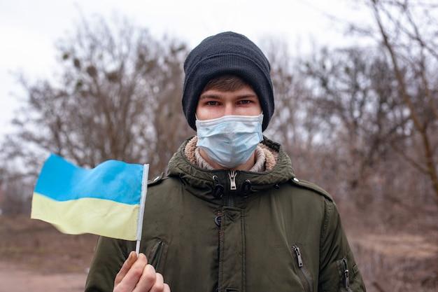 Zieke gemaskerde man met vlag van oekraïne. coronavirus-uitbraak in oekraïne. pandemie covid-2019