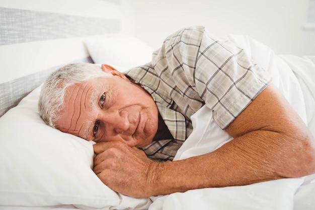 Zieke hogere mens die op bed in slaapkamer ligt
