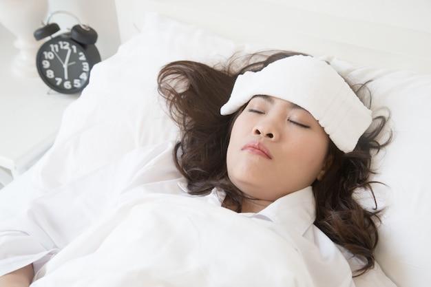 Zieke jonge aziatische vrouw die op bed ligt