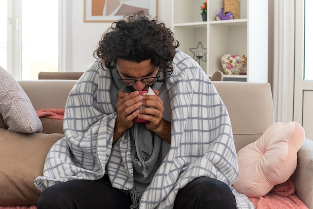 Zieke jonge blanke man in optische bril gewikkeld in plaid met sjaal om zijn nek, vasthoudend en kijkend naar beker zittend op de bank in de woonkamer