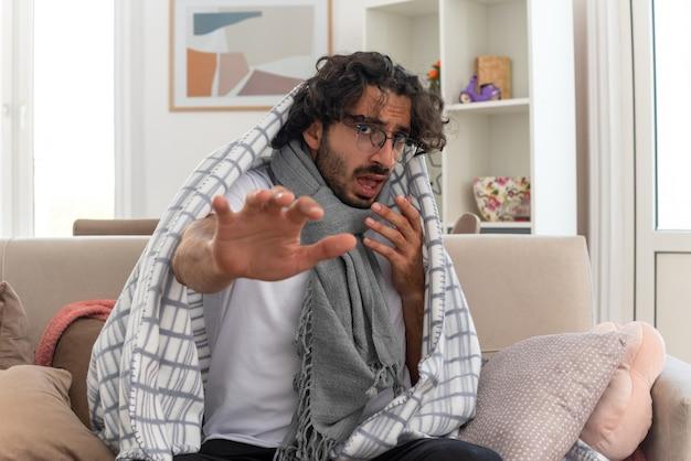 Zieke jonge blanke man met optische bril gewikkeld in plaid met sjaal om zijn nek die zijn hand uitstrekt zittend op de bank in de woonkamer