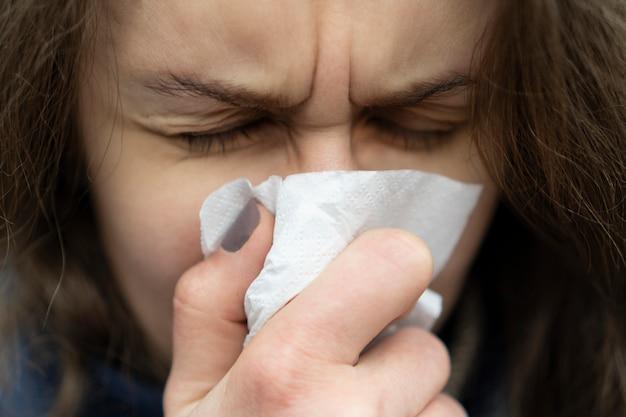 Zieke jonge blanke vrouw haar neus waait in een zakdoek staande op straat bij koud weer