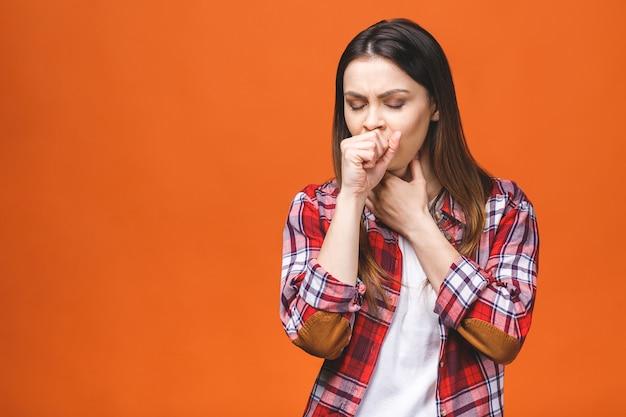 Zieke jonge brunette vrouw in geruit overhemd, met keelpijn, hand op haar nek