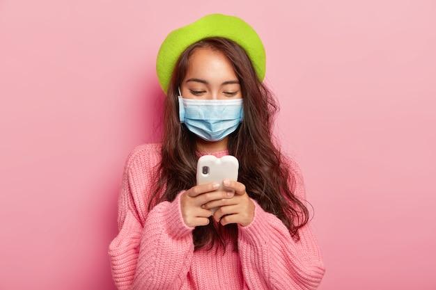 Zieke jonge brunette vrouw met donker haar, gericht in mobiel apparaat, draagt medische masker, heeft problemen met de gezondheid