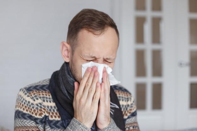 Zieke jonge kerel die thuis niest