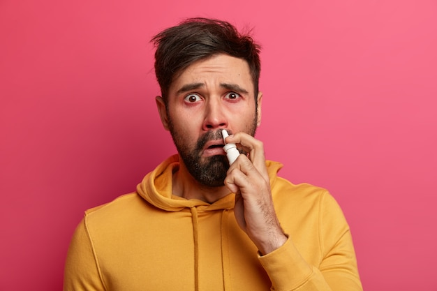 Zieke jonge man die lijdt aan allergie geïsoleerd
