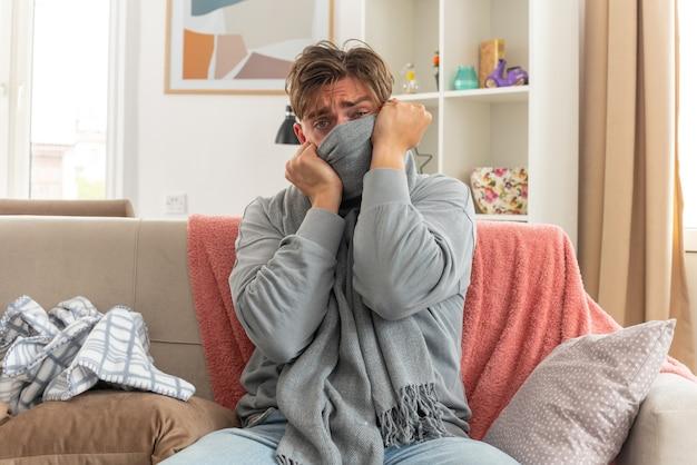 Zieke jonge man die zijn mond bedekt met sjaal zittend op de bank in de woonkamer