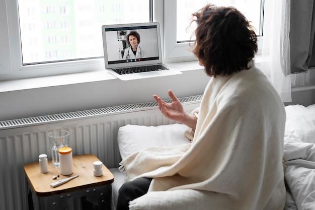 Zieke jonge man in gesprek met zijn dokter online