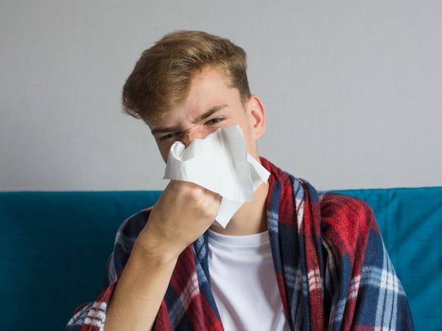 Zieke jonge man zijn neus snuiten in vloeipapier