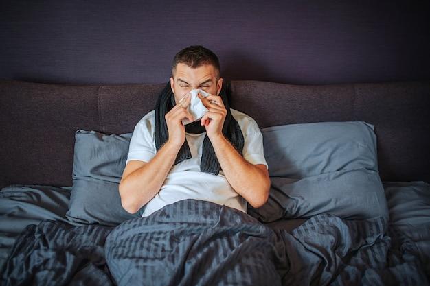 Zieke jonge man zit op bed. hij is bedekt met deken. man niezen in het weefsel. hij lijdt. jonge man voelt zich vreselijk. hij is geconcentreerd op niezen.