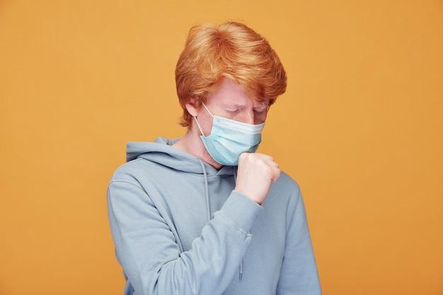 Zieke jonge roodharige man in masker hoesten in de hand op oranje, coronavirus symptoom concept