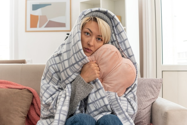 Zieke jonge slavische vrouw met sjaal om haar nek gewikkeld in plaid met winterhoed knuffelend kussen kijkend naar camera zittend op de bank in de woonkamer