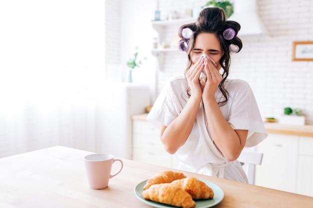 Zieke jonge vrouw dekking neus met weefsel. influenza. croissant en kopje drank op tafel. alleen thuis. huisvrouw leeft onzorgvuldig.