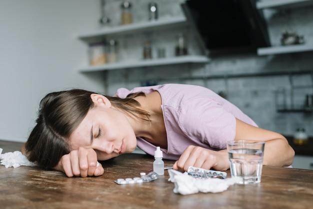 Zieke jonge vrouw die op houten bureau leunt