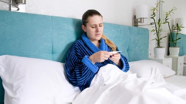 Zieke jonge vrouw die zich onwel voelt temperatuur meten