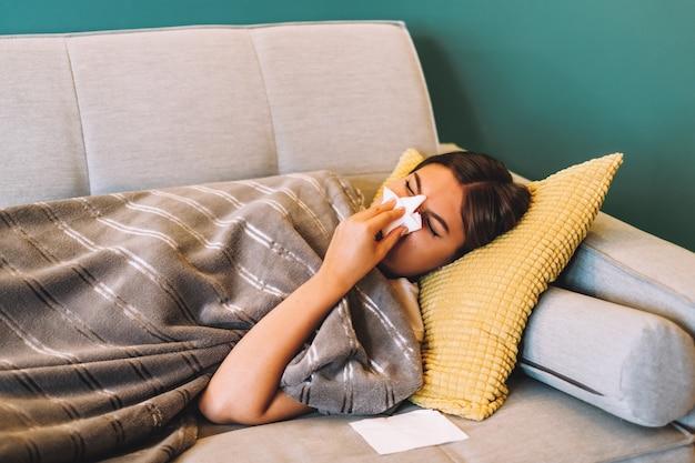 Zieke jonge vrouw haar neus snuiten met behulp van tissues terwijl ze thuis op de bank ligt