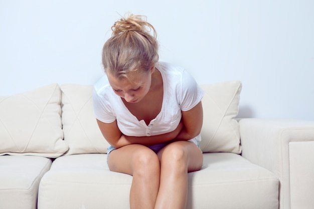 Zieke jonge vrouw met buikpijn. meisje voelt maagpijn