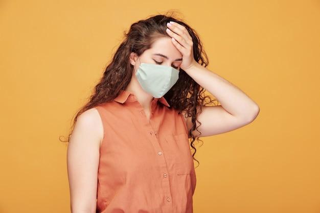 Zieke jonge vrouw met hoofdpijn in beschermend masker haar hoofd aan te raken terwijl ze zich onwel voelt