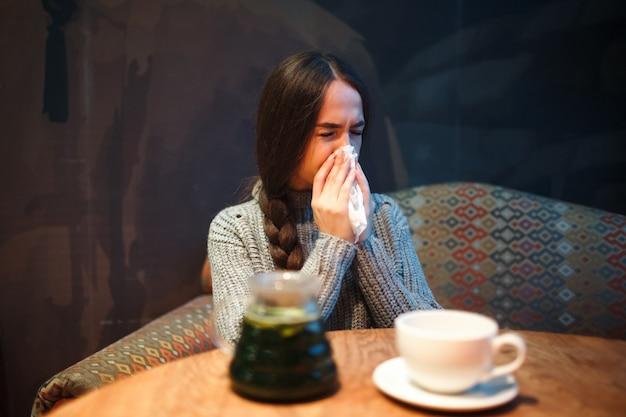 Zieke jonge vrouw met koorts die in weefsel niest