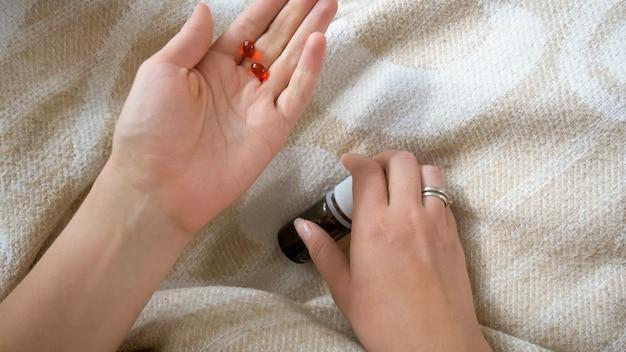 Zieke jonge vrouw met rode pillen of tabletten bij de hand?