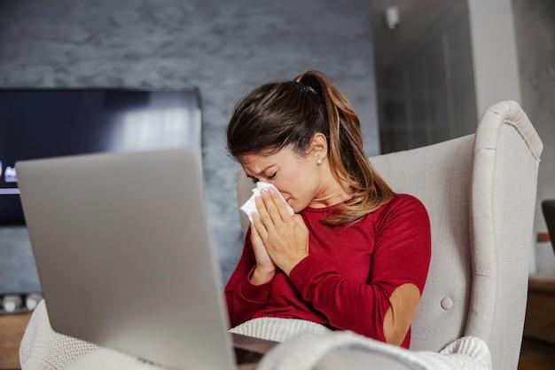 Zieke jonge vrouw om thuis te zitten, haar neus te blazen en laptop op schoot te houden.