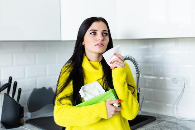 Zieke jonge vrouw snuit haar neus in de keuken.