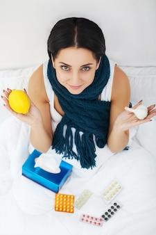Zieke jonge vrouw thuis op de bank, ze bedekt met een deken, neemt temperatuur en blaast haar neus met een tissue