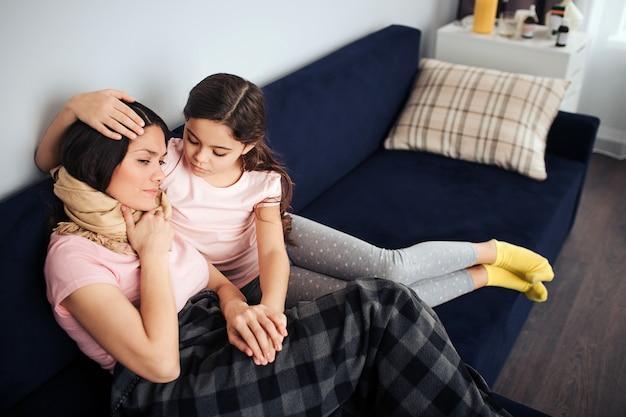 Zieke jonge vrouw zit op de bank samen met haar dochter. kind omhelst moeder hoofd. ze kijkt haar aan. kid touch vrouw de hand. ze probeert haar te troosten.