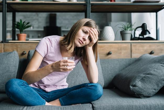 Zieke jonge vrouw zittend op de bank met een glas water