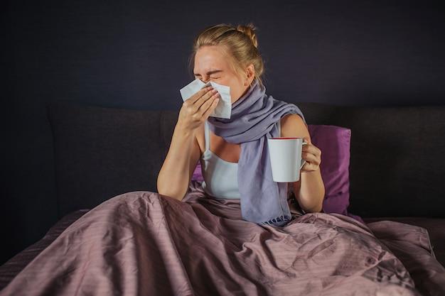 Zieke jonge vrouwelijke persoon die in wit servet niest. ze houdt een witte beker in een andere hand. jonge vrouw is ziek. ze zit op bed en bedekt met deken. meisje heeft sjaal om nek.