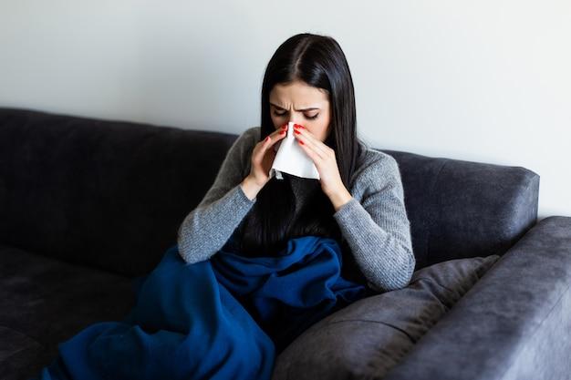Zieke jonge vrouwenzitting op bank die haar neus thuis in de woonkamer blazen