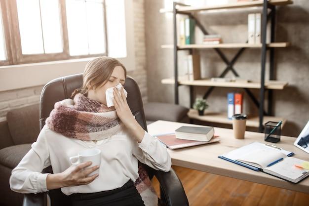 Zieke jonge zakenvrouw zitten aan tafel in de kamer en niezen. ze lijdt aan ziekte. vrouw kan niet werken.